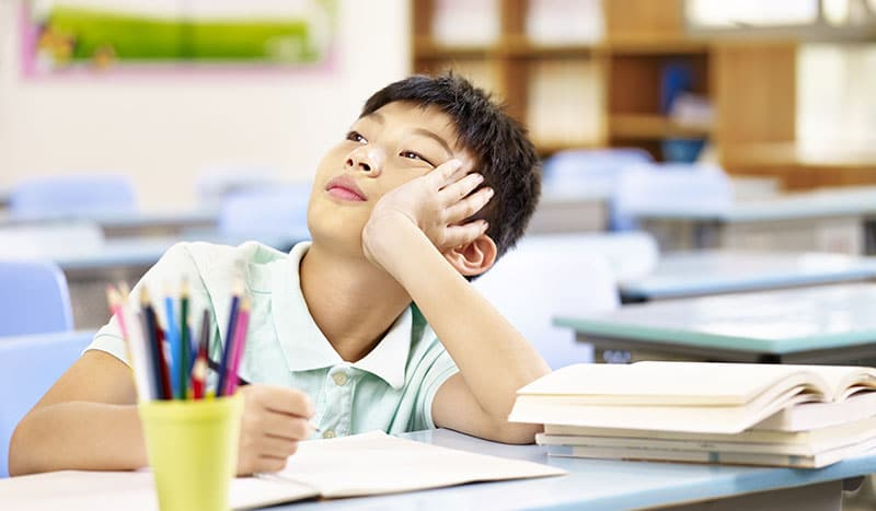 young male student sitting at classroom daydreaming
