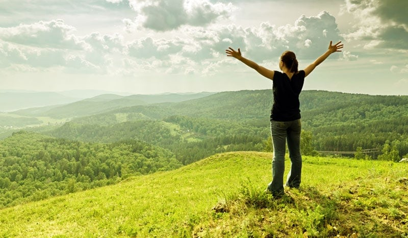 woman standing on hilltop with arms outstretched