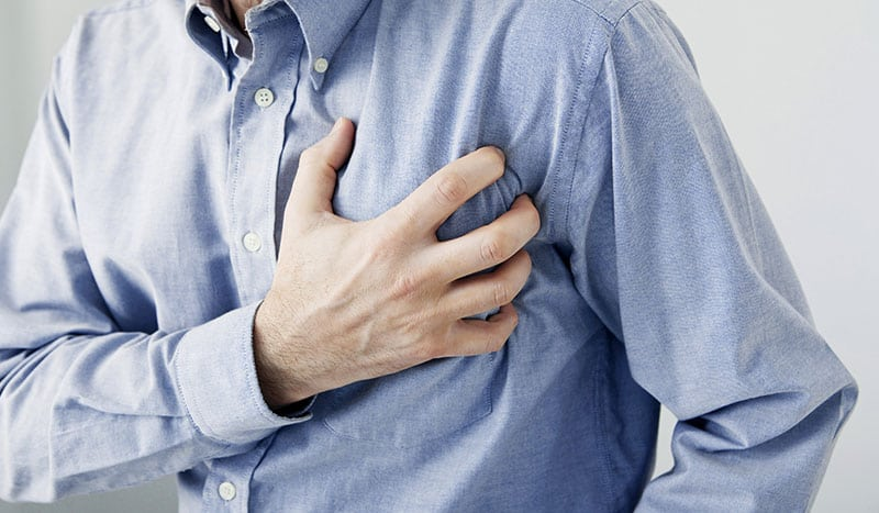 man clutching his chest, experiencing symptoms of cardiovascular disease