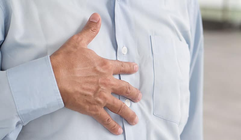 close-up of man with hand on stomach, experiencing digestive disorder