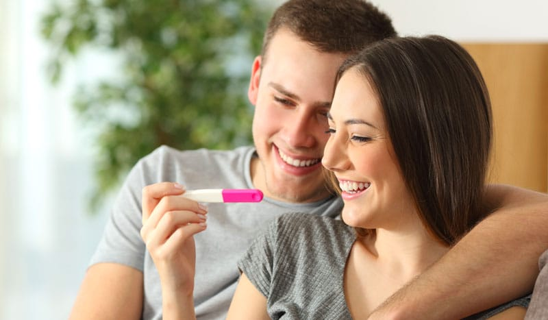happy couple looking at pregnancy test results