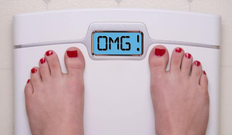 "woman's feet standing on a scale that reads ""OMG!"""