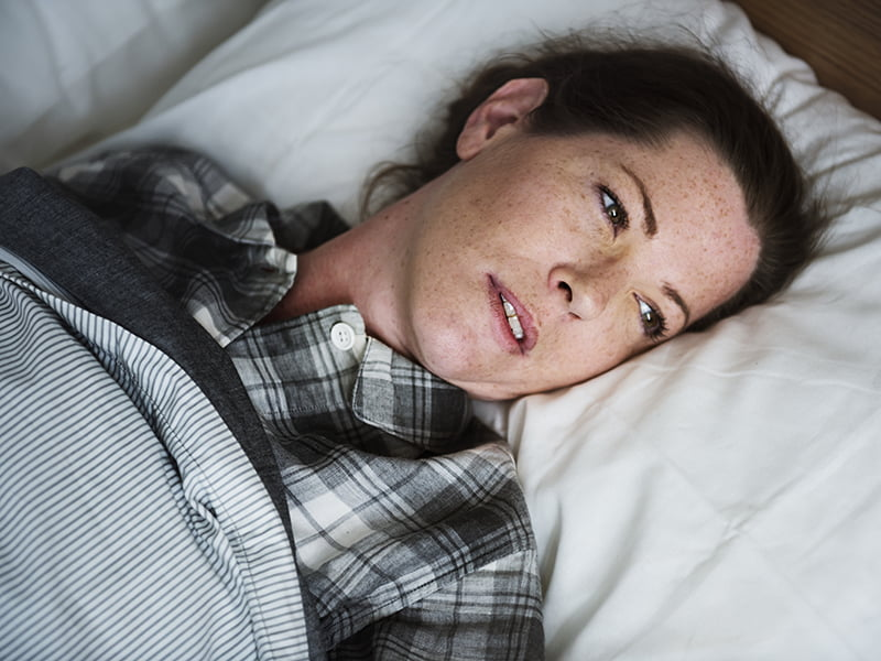 photo of woman in plaid pajamas in bed, having just woken up