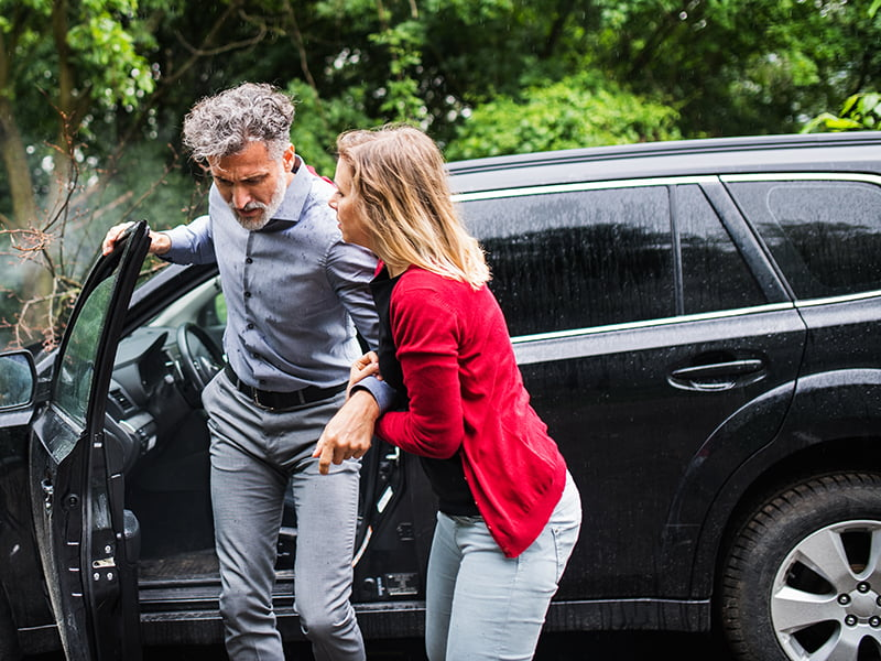 young woman helping a man get out of a car