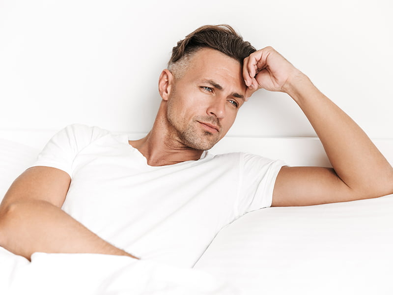 focused man laying in bed suffering from low immune system