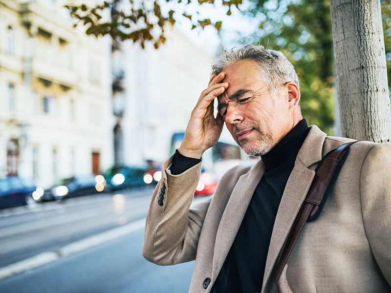 mature businessman in pain standing on city sidewalk