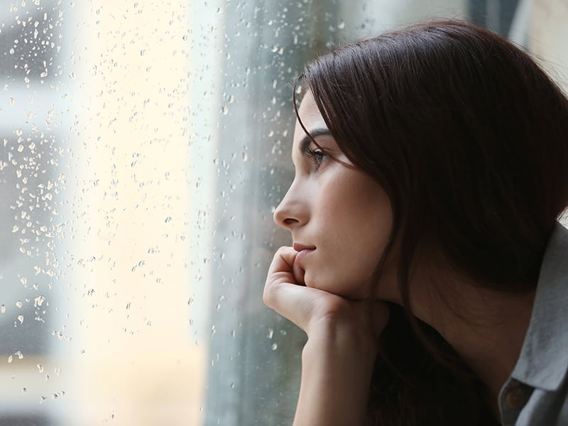 young woman looking out rain streaked window