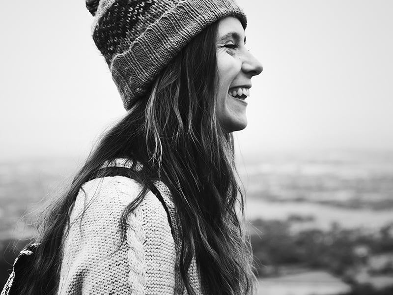 black and white side profile of smiling woman wearing knit hat