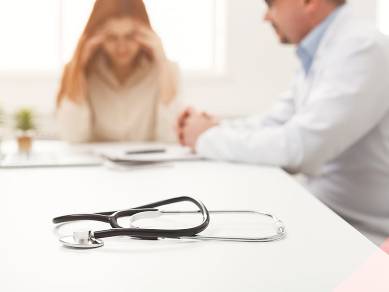 stethoscope on the desk with patient and doctor in background