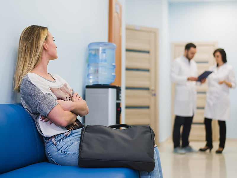 woman waiting at hospital with doctors in background