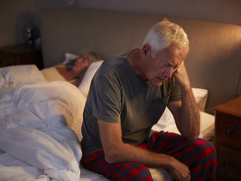 worried senior man in bed at night suffering with headache