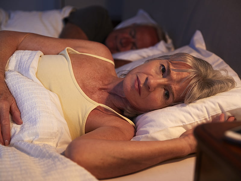 older woman lying in bed with insomnia